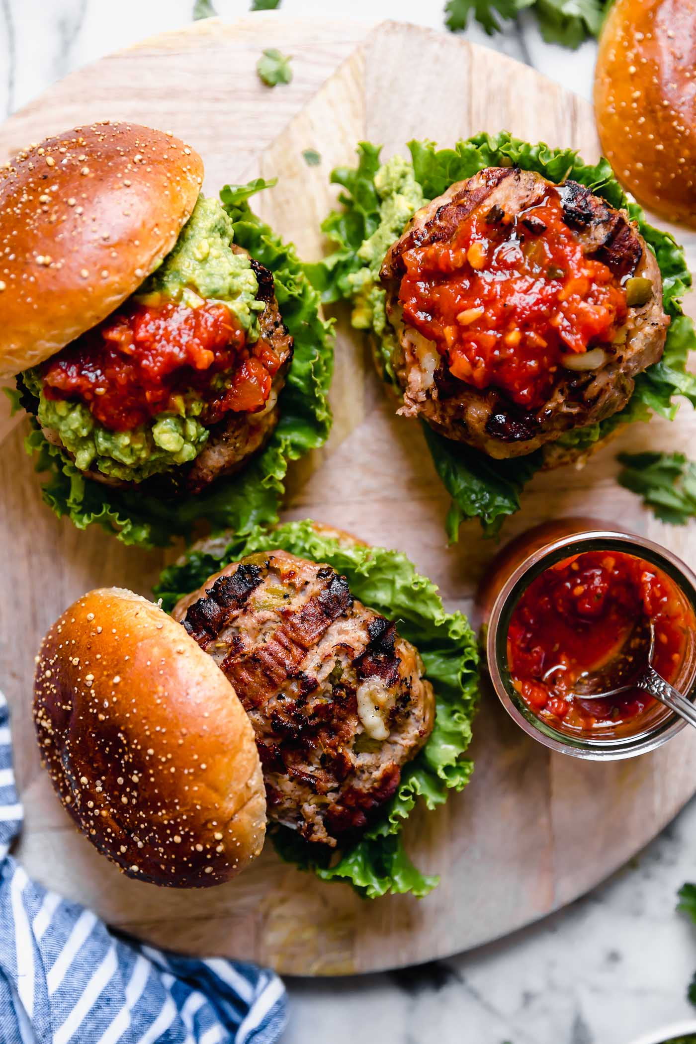 Stuffed southwest turkey burgers arranged on a round wooden board. One burger is topped with mashed avocado. Two of the burgers are topped with salsa. On the board with the burgers is a jar of salsa with a spoon in it, a striped blue linen, and some fresh cilantro.