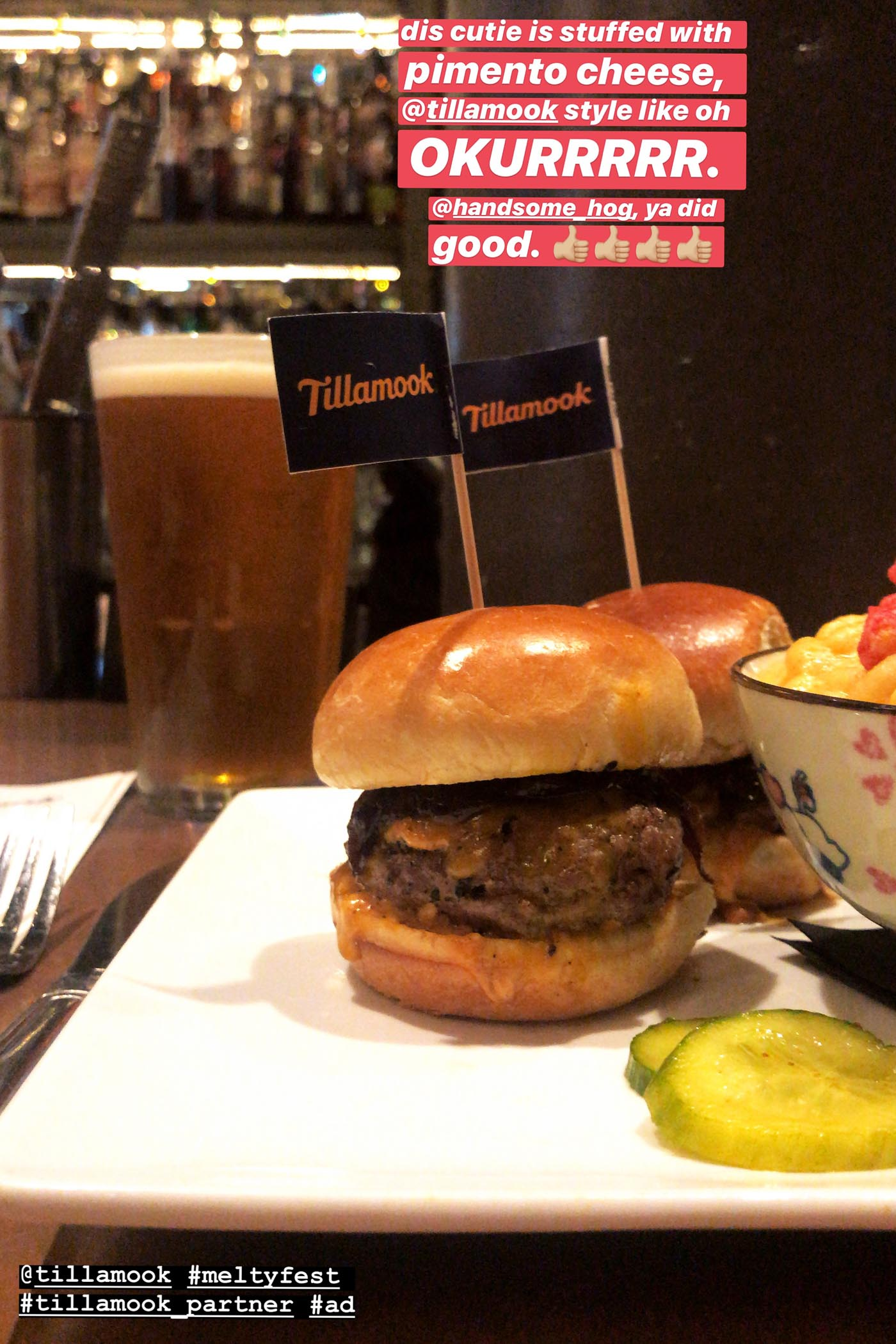 "Mini cheeseburger on a plate with mini blue flag that says ""Tillamook"" coming out of it."