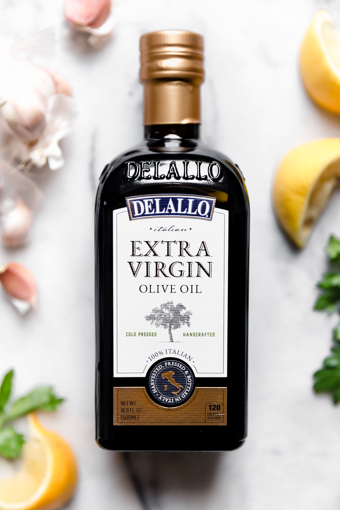 DeLallo olive oil bottle shown on a white marble surface surrounded by lemon wedges, whole garlic cloves & parsley.