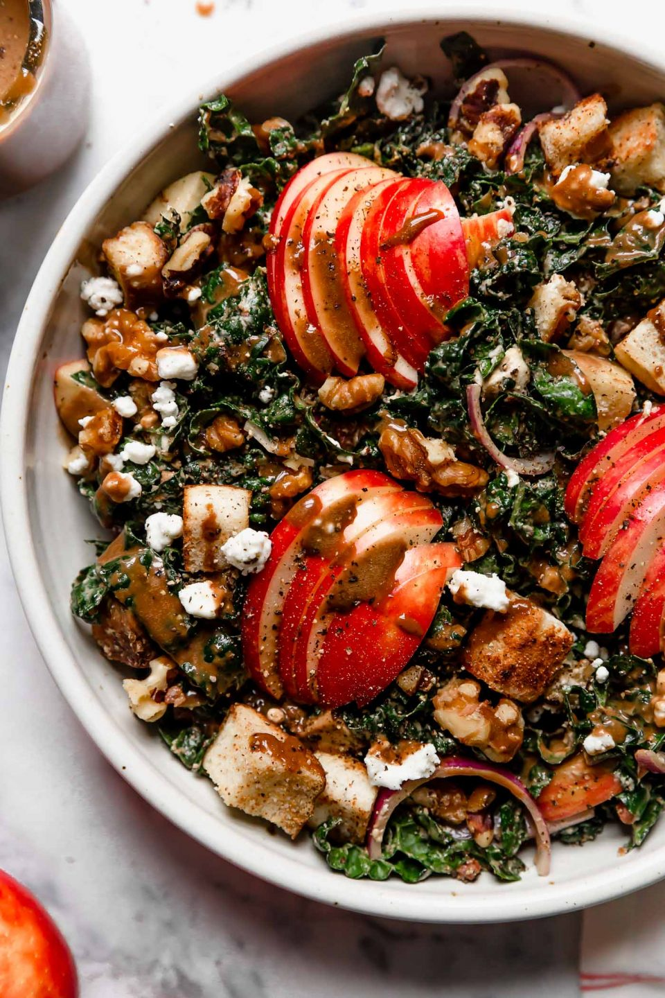 Tossed Autumn Kale salad in a cream ceramic bowl on a white marble surface. The salad is topped with clusters of sliced honeycrisp apples & croutons, & an extra drizzle of maple balsamic vinaigrette.
