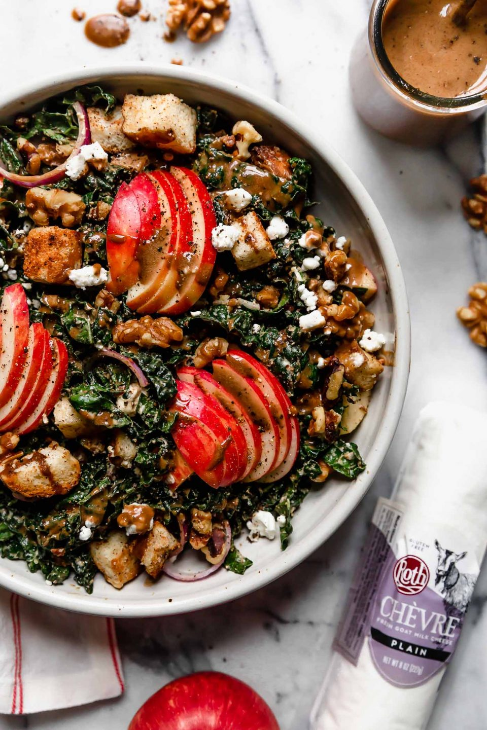 Tossed Autumn Kale salad in a cream ceramic bowl on a white marble surface. The salad is topped with clusters of sliced honeycrisp apples & croutons, & an extra drizzle of maple balsamic vinaigrette. An 8 oz log of Roth Plain Chèvre is sitting next to the salad.