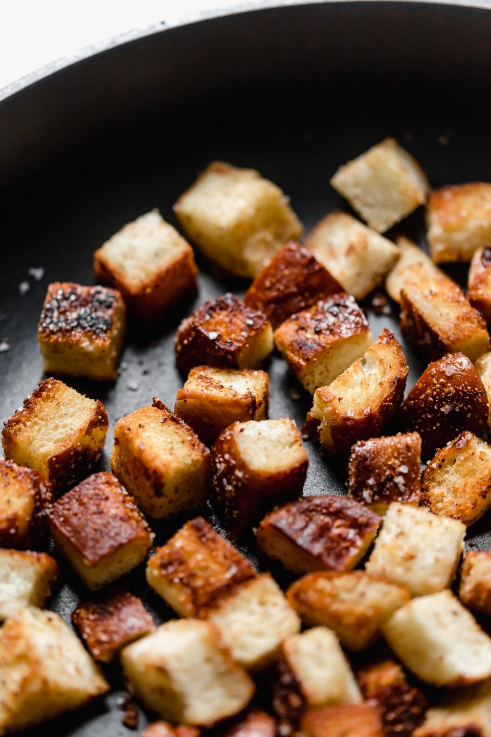 Close up shot of pancetta-pretzel croutons toasting in a black skillet.