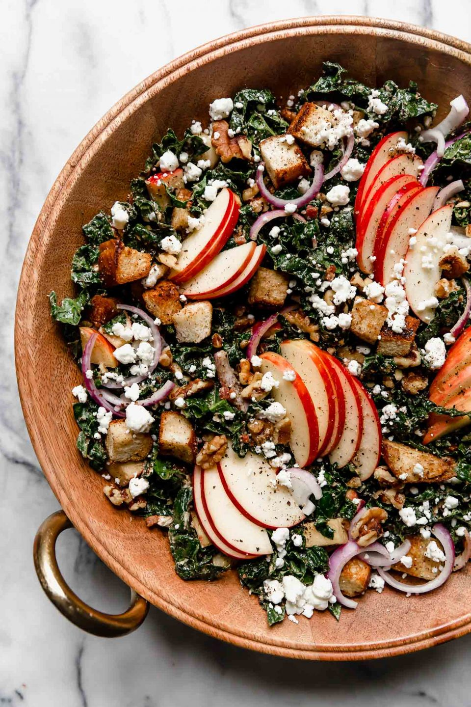 Tossed Autumn Kale salad in a large wooden serving bowl sitting on a white marble surface. The salad is topped with clusters of sliced honeycrisp apples & croutons.