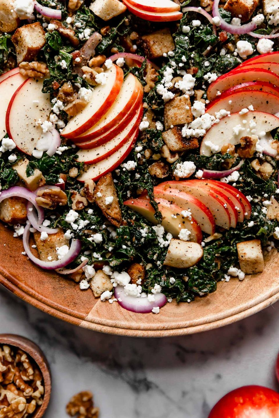 Tossed Autumn Kale salad in a large wooden serving bowl sitting. The salad is topped with clusters of sliced honeycrisp apples & croutons. The serving bowl is atop a white marble surface, next to honeycrisp apples & whole walnuts.