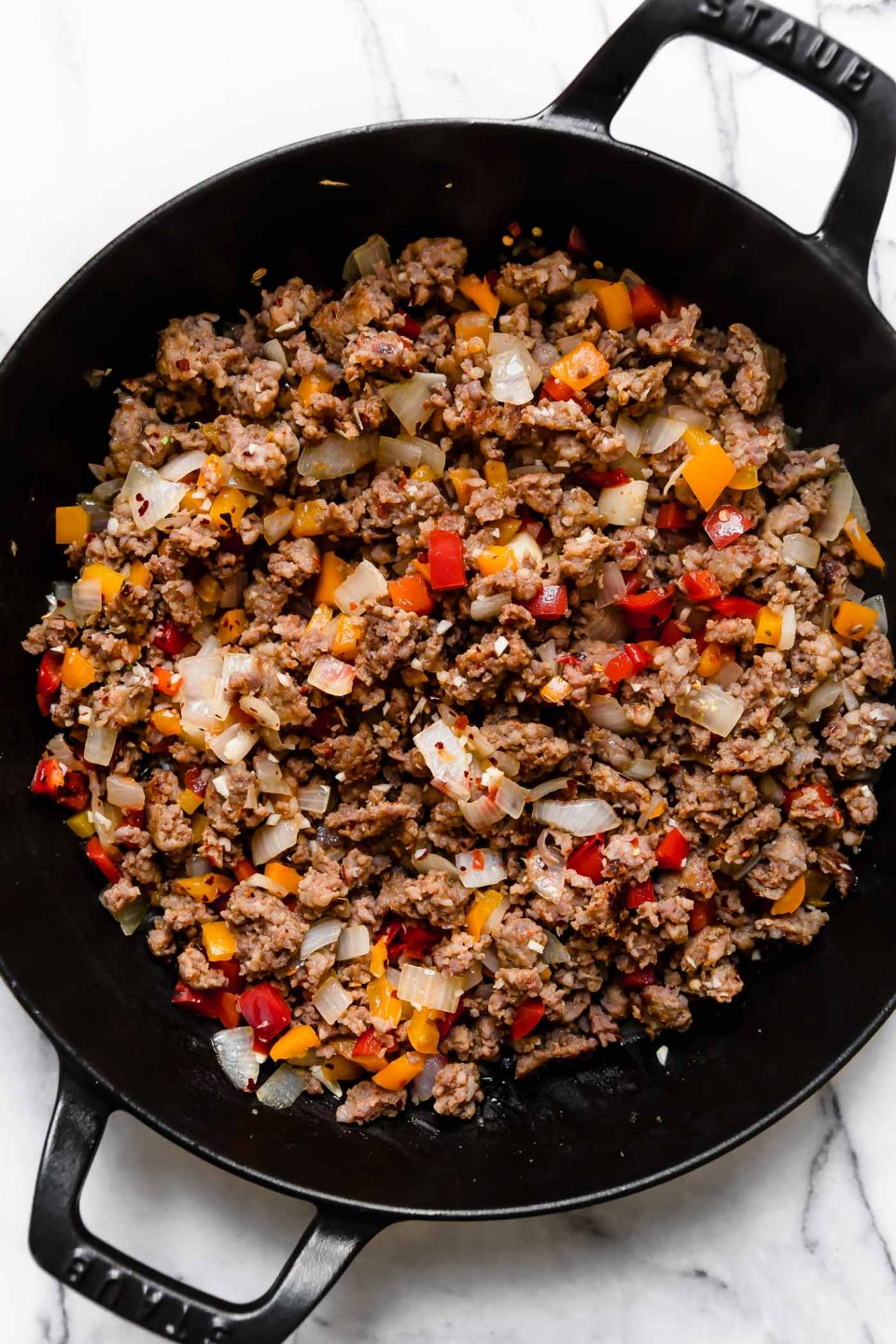 Step 2 of making sausage peppers pasta: browned sausage, bell peppers & onions in large skillet.