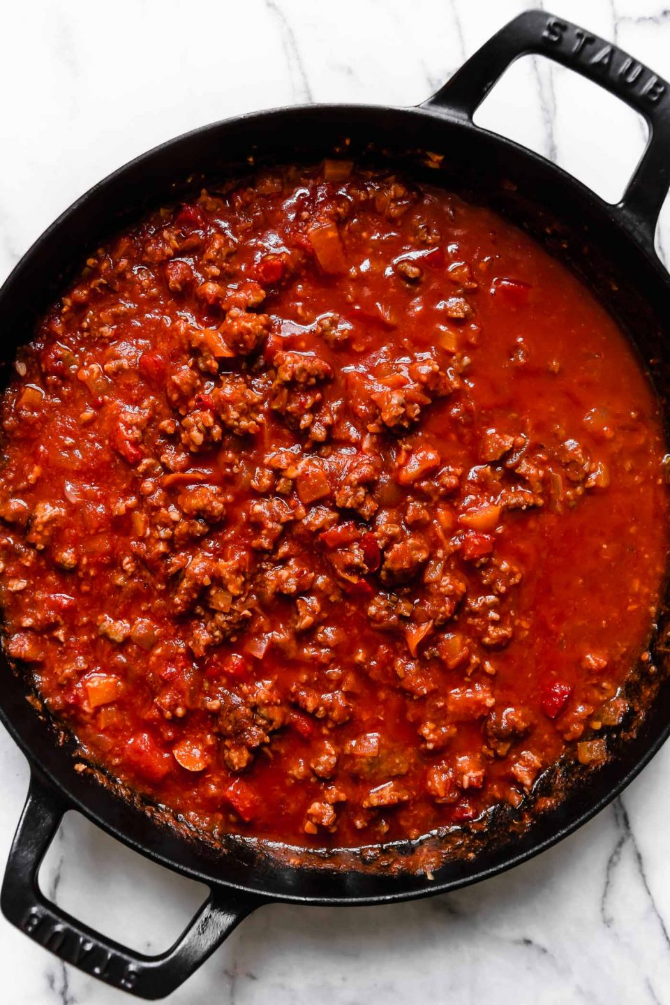 Italian Sausage and peppers pasta sauce in large black skillet.