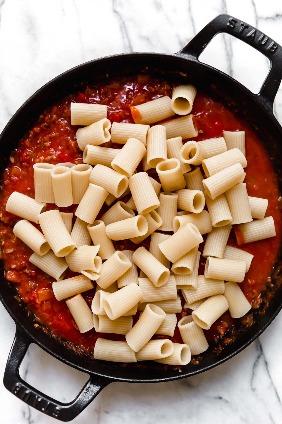 Adding rigatoni pasta to Italian Sausage and peppers pasta sauce in large black skillet.