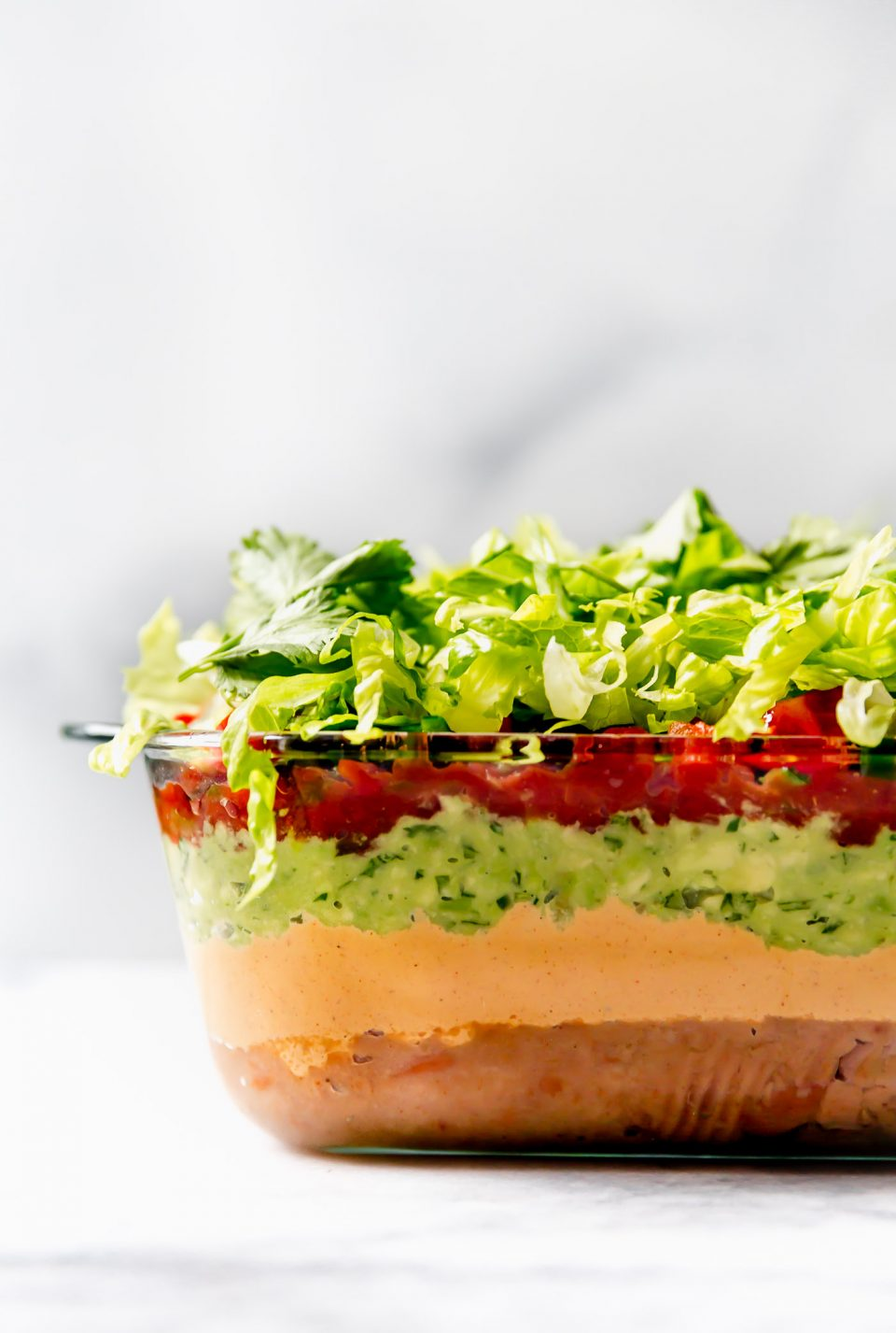 Straight-on photo of this vegan 7-Layer Dip recipe shown in clear Pyrex DEEP baking dish.