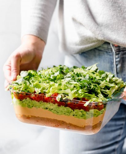 Woman in blue jeans & a gray sweater holding Vegan 7-Layer Dip in front of her.