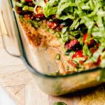 Straight-on photo of this vegan 7-Layer Dip recipe shown in clear Pyrex DEEP baking dish. The dish is sitting on a light wood board, with some of the dip removed from the container.