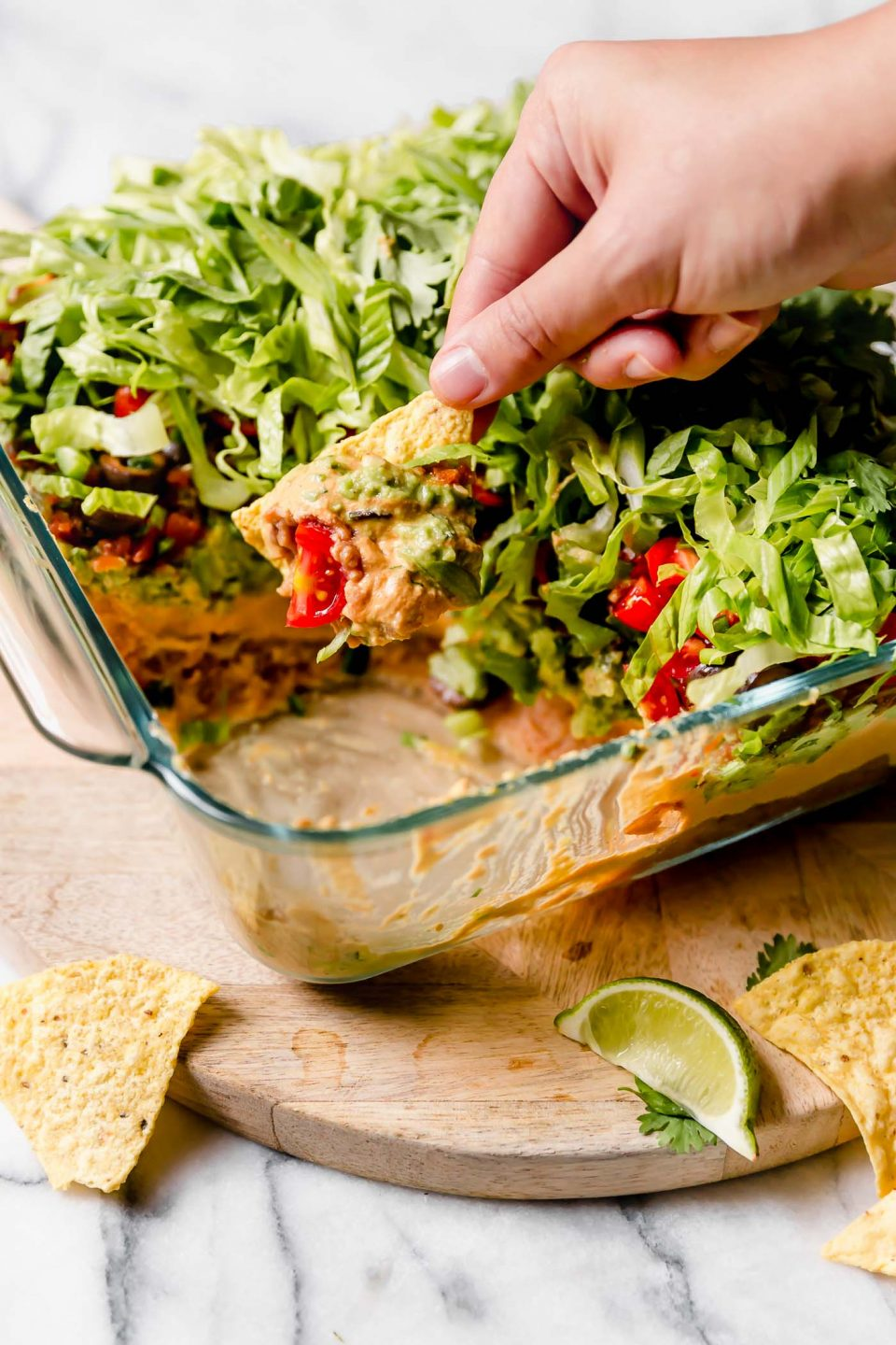 Straight-on photo of this vegan 7-Layer Dip recipe shown in clear Pyrex DEEP baking dish. The dish is sitting on a light wood board, with some of the dip removed from the container. Woman's hand is reaching in with a tortilla chip to remove some of the dip.