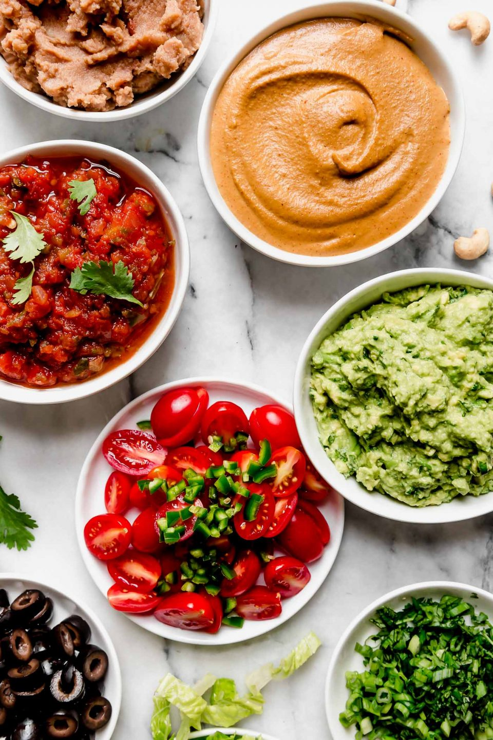 Vegan 7-Layer Dip Recipe Ingredients (refried beans, cashew queso, smashed avocado, salsa of choice, tomatoes, jalapeno peppers, olives, lettuce & cilantro)