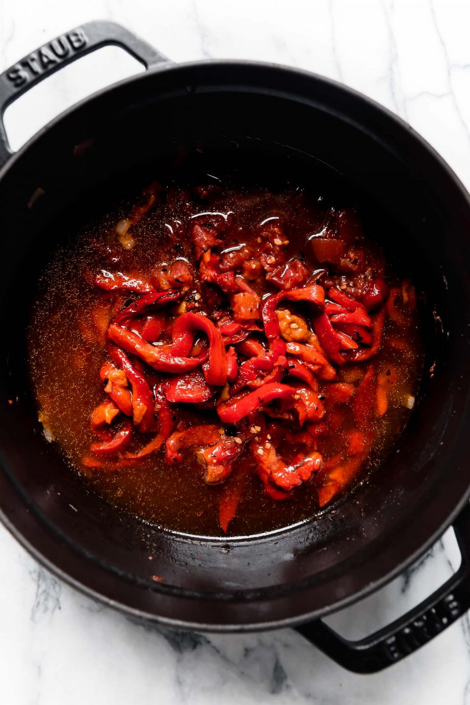Roasted Red Peppers, crushed tomatoes, & veggie stock added to the black Staub Dutch oven for Creamy Roasted Red Pepper Soup