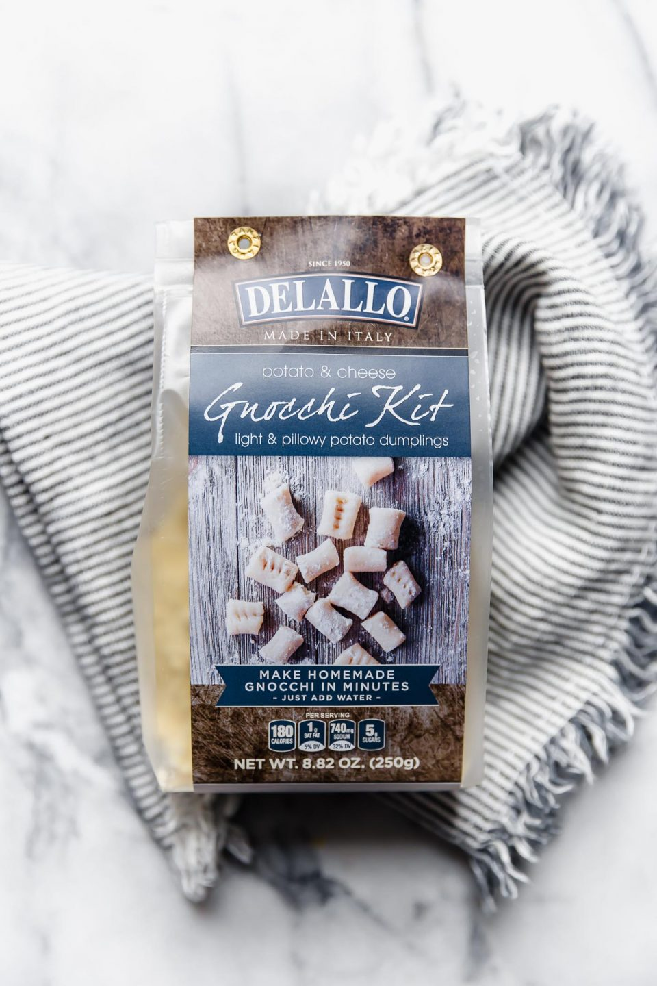 DeLallo's brand new Gnocchi Kit, sitting on striped linen napkin atop a white marble surface