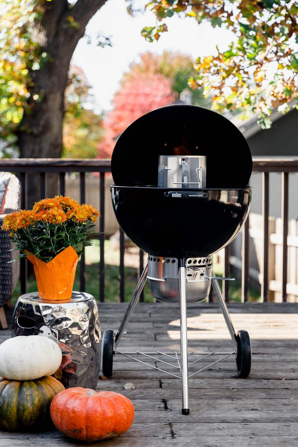 Weber 22-inch Kettle Grill from The Home Depot. Grill is open, with a charcoal chimney inside. The grill is on a deck, surrounded by orange mums & pumpkins. There is a tree in the backyard with orange and green leaves.