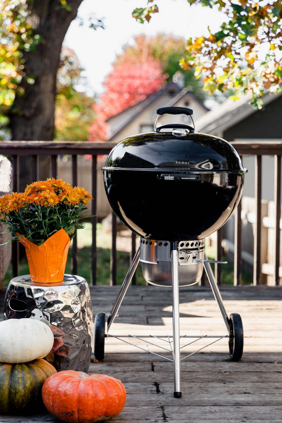 Weber 22-inch Kettle Grill from The Home Depot. Grill is on a deck, surrounded by orange mums & pumpkins. There is a tree in the backyard with orange and green leaves.
