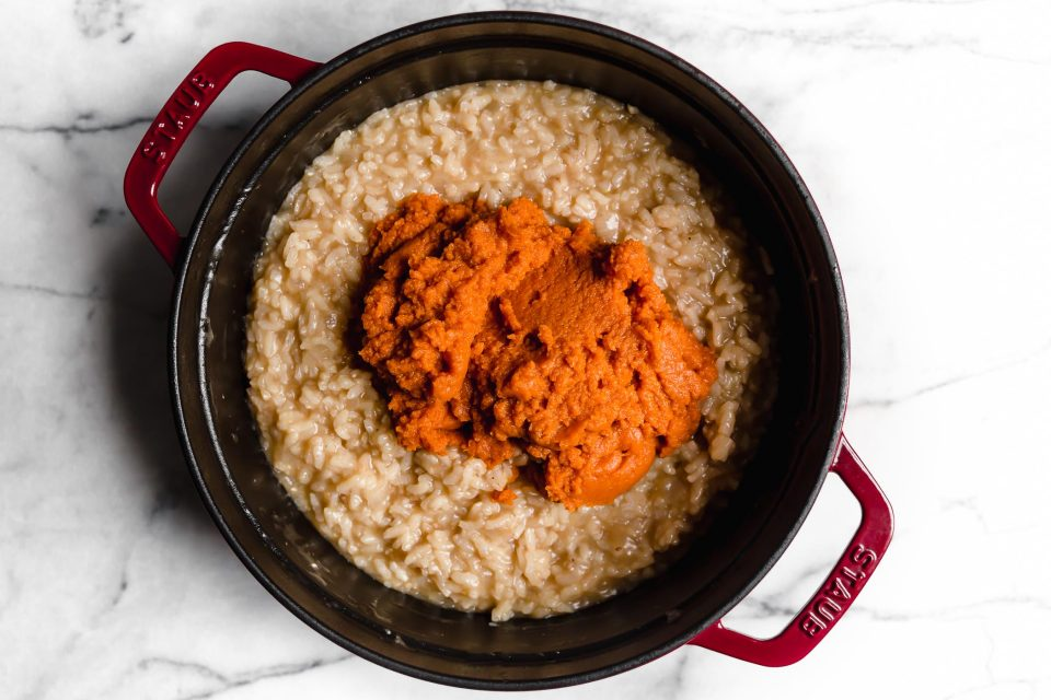 Adding pumpkin to no-stir risotto for pumpkin risotto.