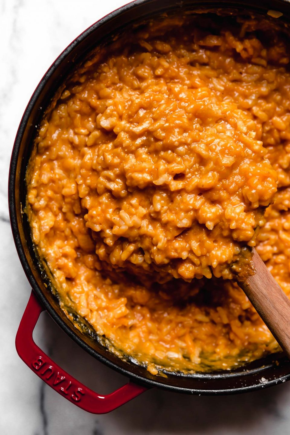 Pumpkin risotto shown in a large red Dutch oven. A wooden spoon is stirring the creamy risotto.