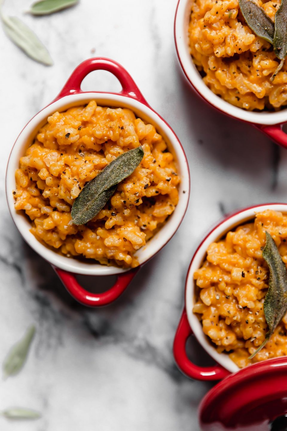 Individual portions of pumpkin risotto served in small red ramekins, topped with crispy fried sage.