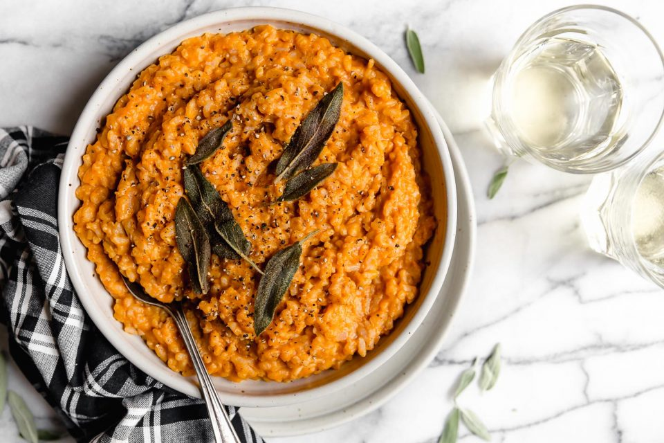 No-stir pumpkin risotto served in a large ceramic bowl, topped with crispy fried sage. Surrounding the risotto are a plaid striped napkin & 2 glasses of white wine.