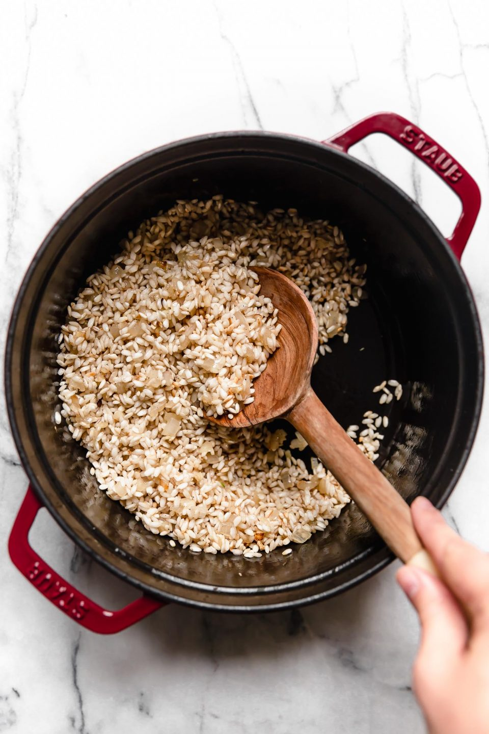 Wooden spoon stirring Arborio rice for pumpkin risotto recipe.
