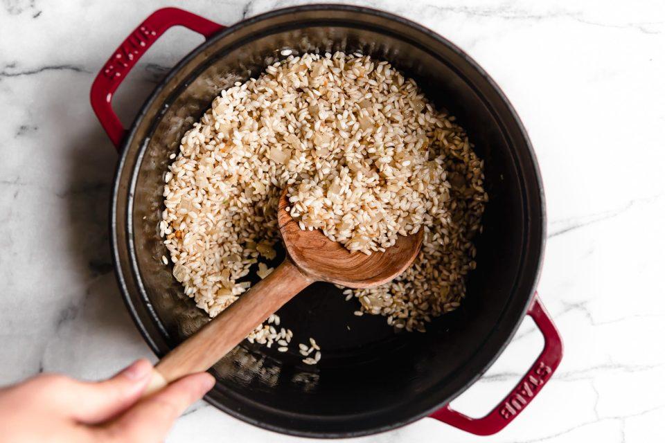 Wooden spoon stirring Arborio rice for pumpkin risotto recipe.