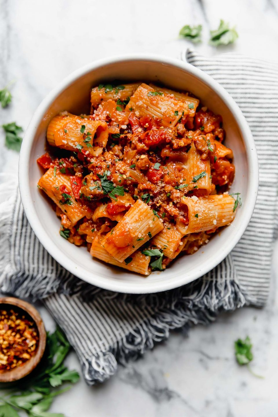 Italian Sausage & peppers pasta served in a white bowl sitting on a striped linen napkin atop a white marble surface surrounded by fresh parsley leaves, & a small wooden bowl filled with crushed red pepper flakes.