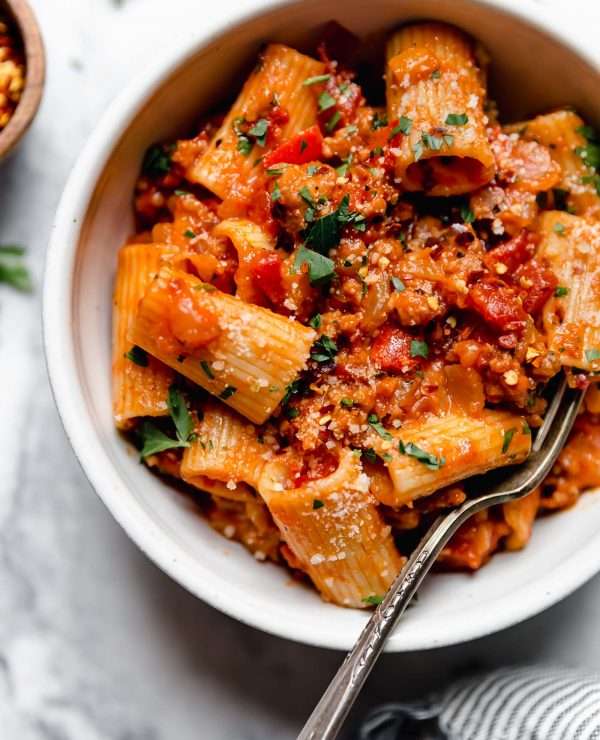 Italian Sausage & peppers pasta served in a white bowl sitting on a white marble surface surrounded by a striped linen napkin, fresh parsley leaves, & a small wooden bowl filled with crushed red pepper flakes.