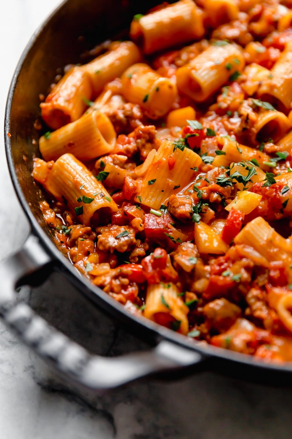 Italian sausage & peppers pasta in a large Staub skillet, topped with fresh parsley. The skillet is sitting on a white marble surface.