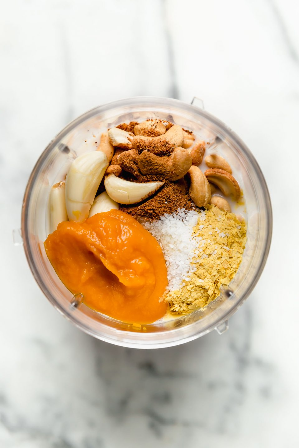 Vegan pumpkin cream sauce ingredients shown in a blender before blending.