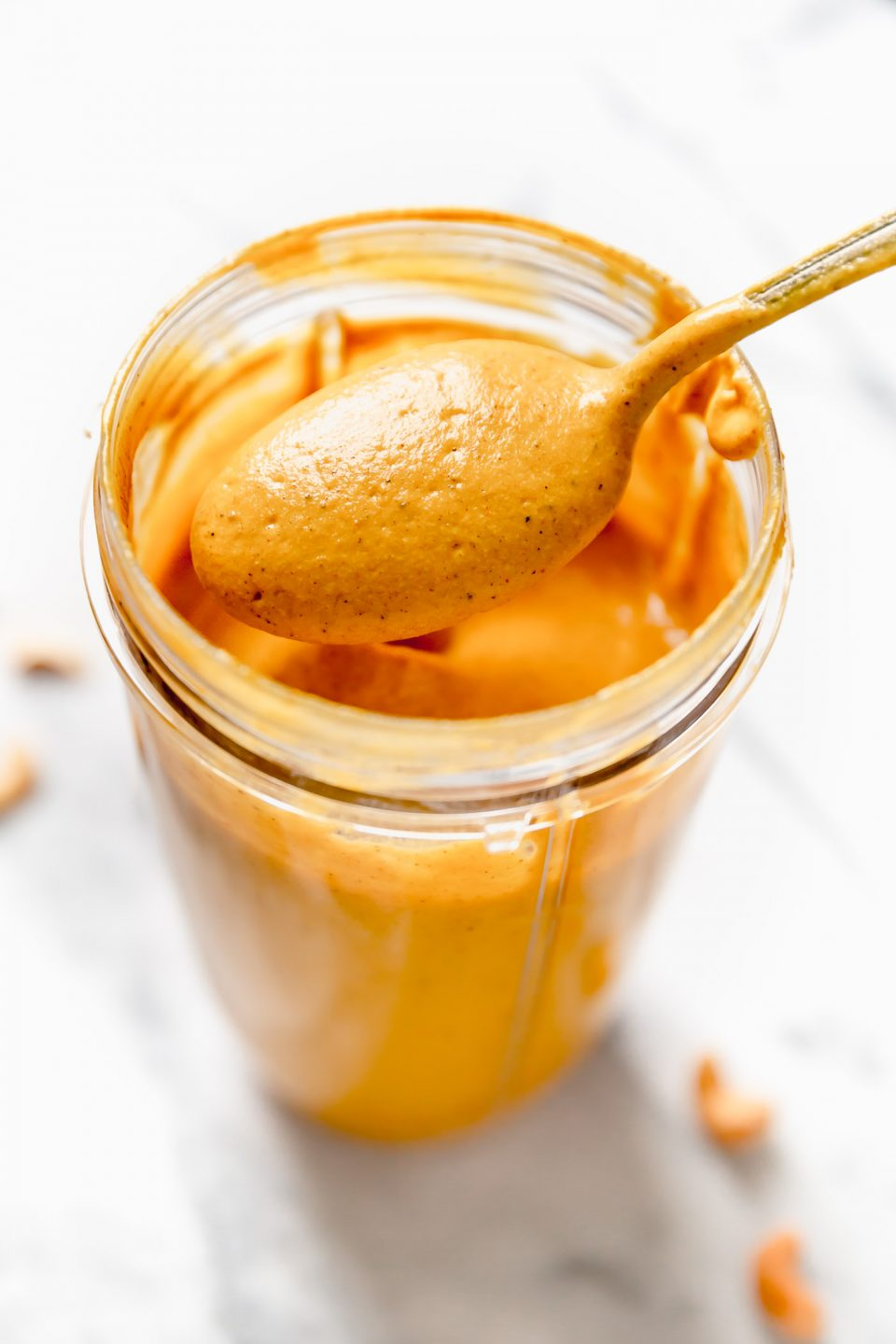 Vegan pumpkin cream sauce shown in a blender after blending. A spoon is lifting some of the sauce out of the blender.