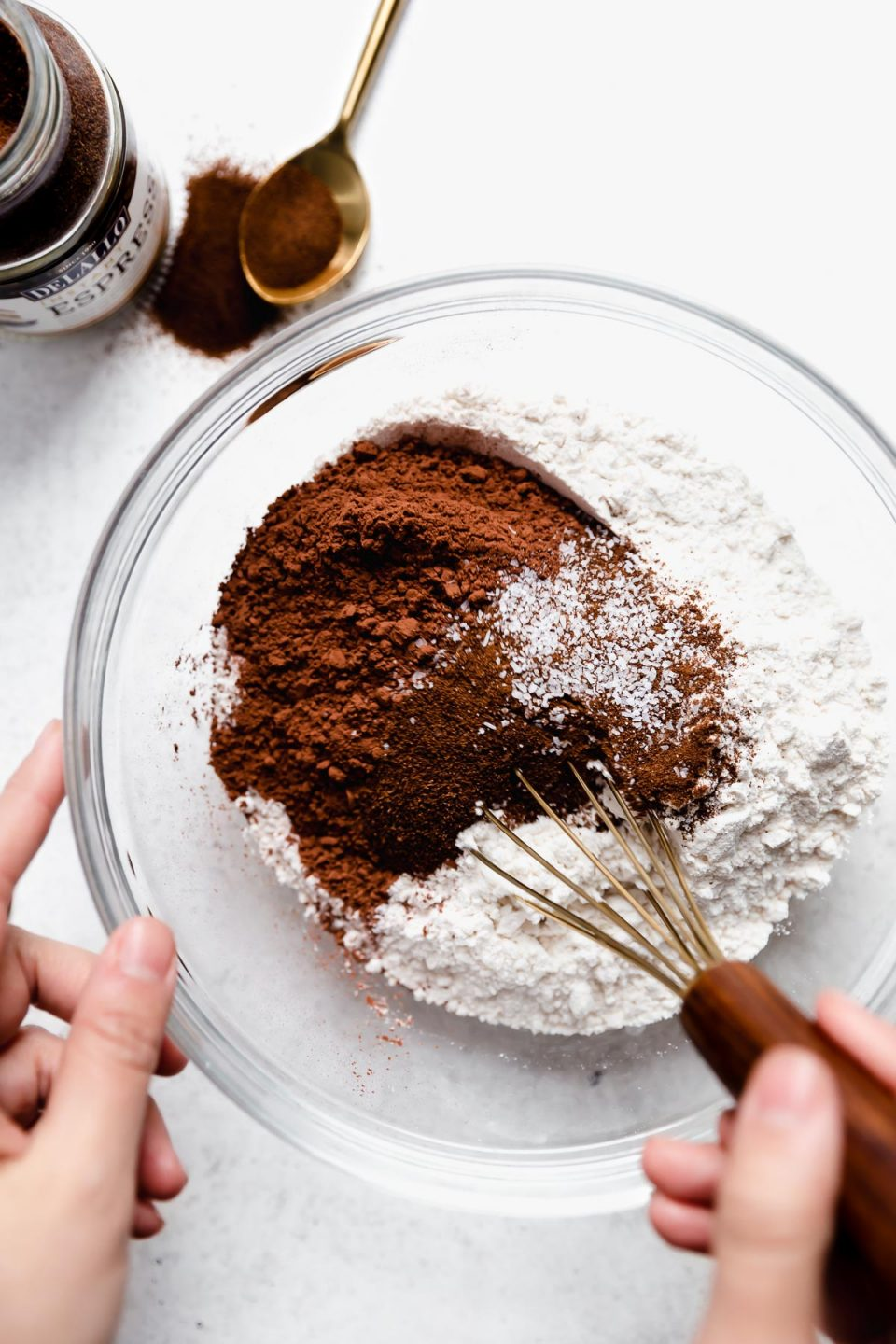 Thumbprint cookies dry mix (flour, cocoa powder, espresso powder & salt) in a large mixing bowl. A woman's hands are reaching into the bowl with a small whisk. At the top of the frame sits a bottle of DeLallo Instant Espresso Baking powder.