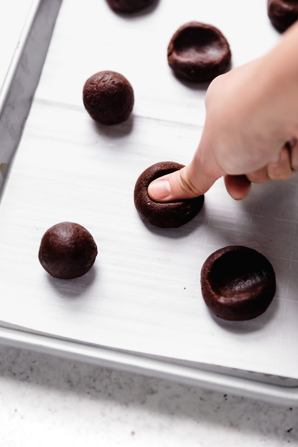 Chocolate thumbprint cookie dough balls placed on a parchment-lined baking sheet. A woman's thumb is pressing down on one of the cookies to create an indentation in the center.