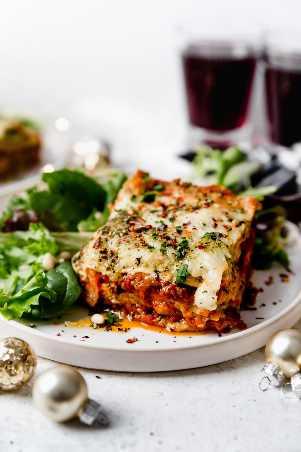 Christmas Eve Lasagna on a small white plate, atop a white surface surrounded by small Christmas ornaments & a glass of red wine.