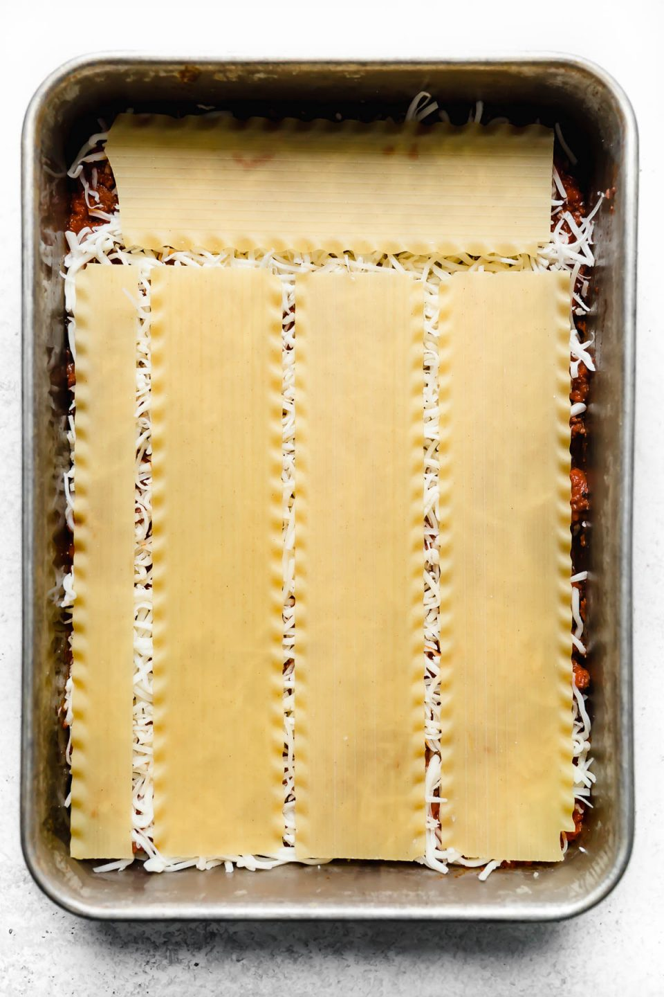 How to assemble & layer lasagna: adding a layer of no-boil pasta noodles to the baking dish.