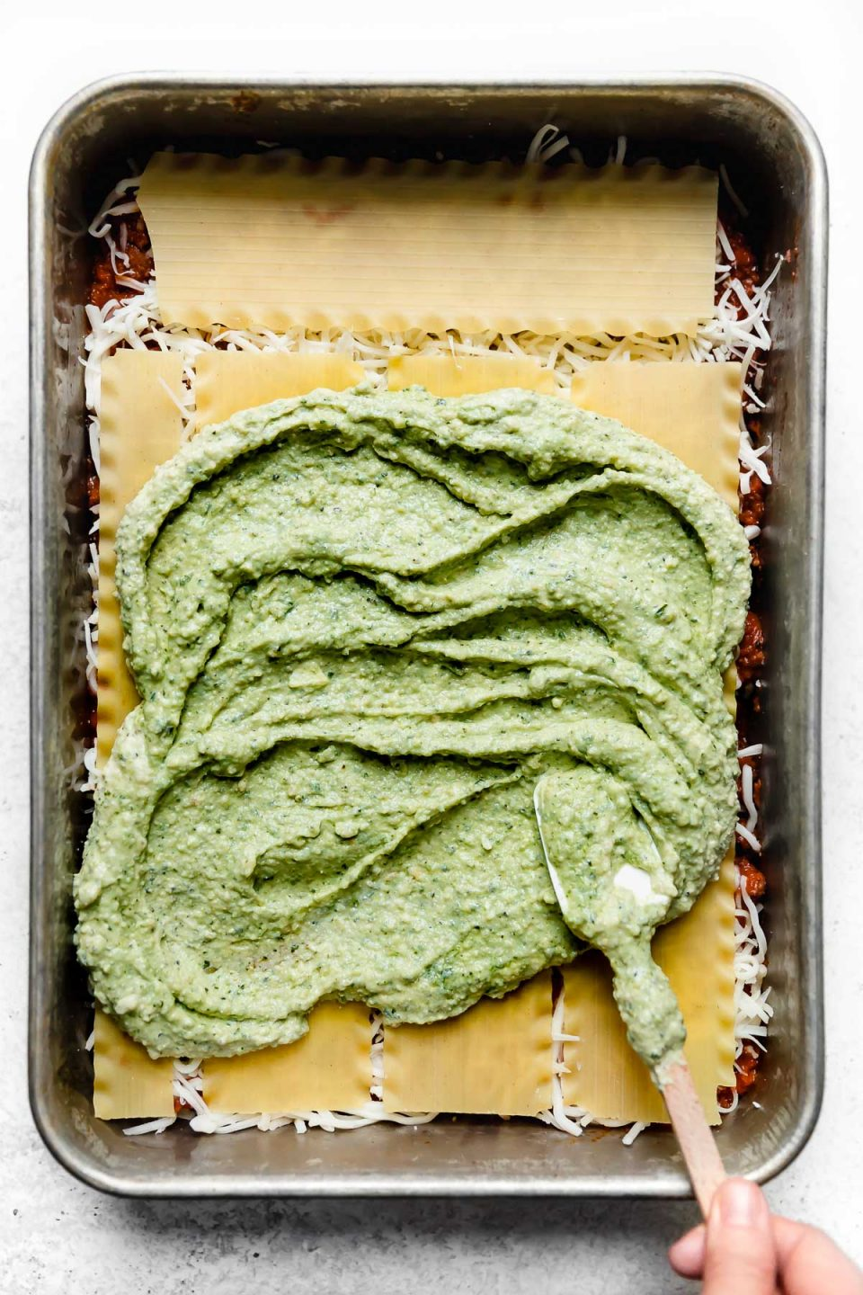 How to assemble & layer lasagna: spreading basil pesto ricotta over a layer of noodles.