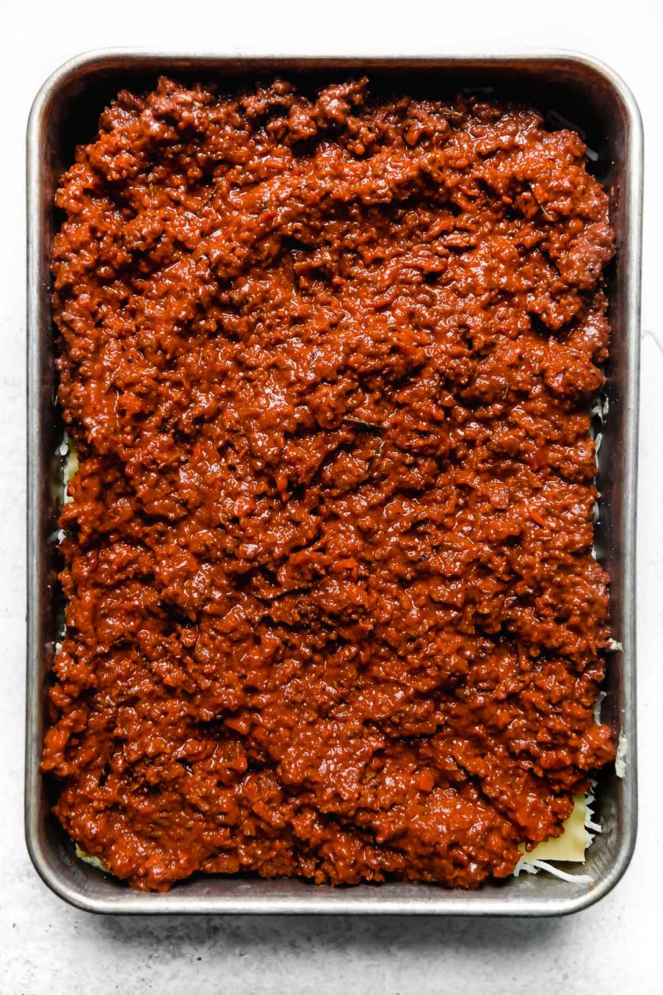 How to assemble & layer lasagna: spreading homemade bolognese sauce over the pasta.
