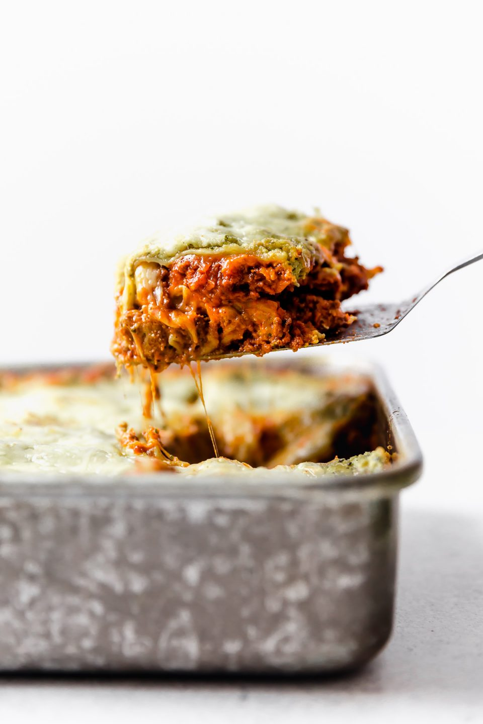 Lifting a slice of lasagna out of its metal baking dish.