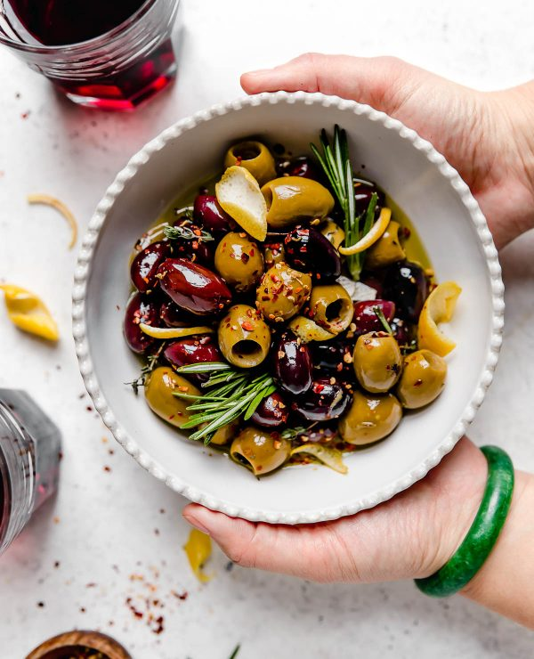 Homemade marinated olives served in a white dish with scalloped edges. The bowl is atop a white surface, surrounded by fresh rosemary, lemon peel, a small wooden bowl with red chili flakes, & a few glasses of red wine. A woman's hands are reaching into the photo, holding the bowl of olives.