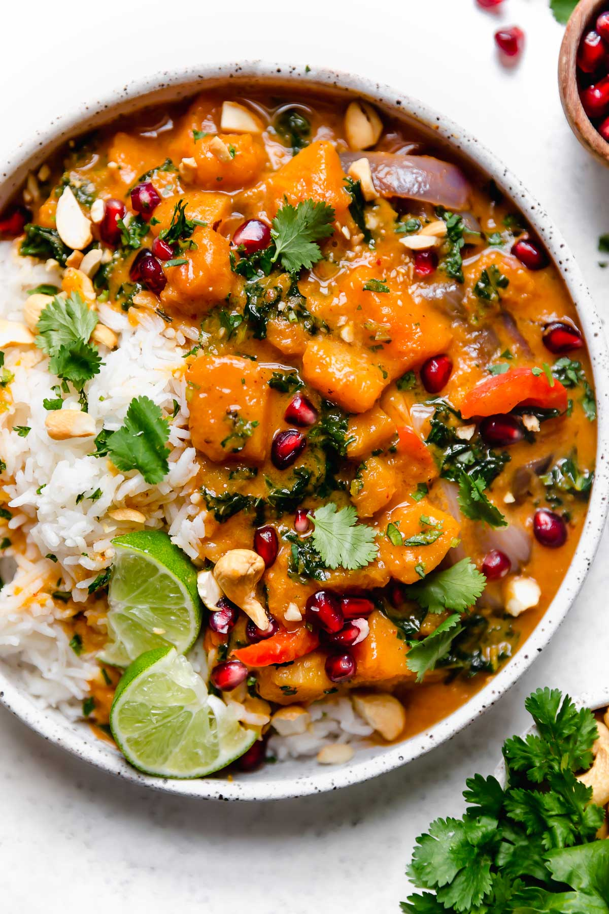 Butternut Squash Red Curry in a speckled white bowl, with white rice, chopped cilantro, cashews, & pomegranate arils.