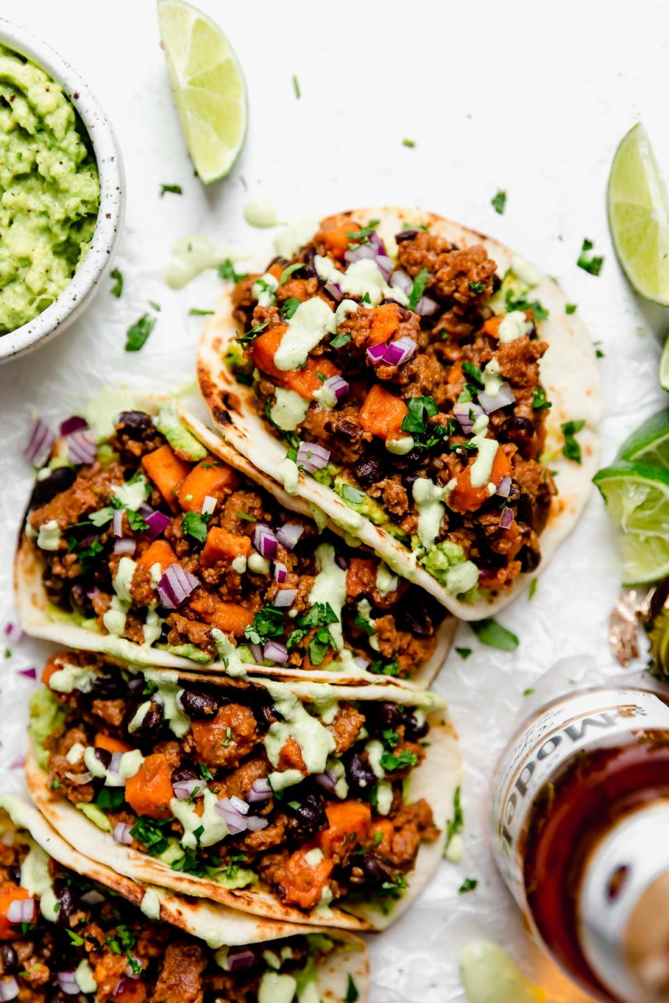 Close up photo of chorizo Sweet Potato Tacos arranged on a white surface. The tacos are topped with a drizzle of homemade cilantro lime crema. Surrounding the tacos are small bowls of taco toppings (pickled red onions, guacamole, crema, etc.) & a bottle of Modelo beer.