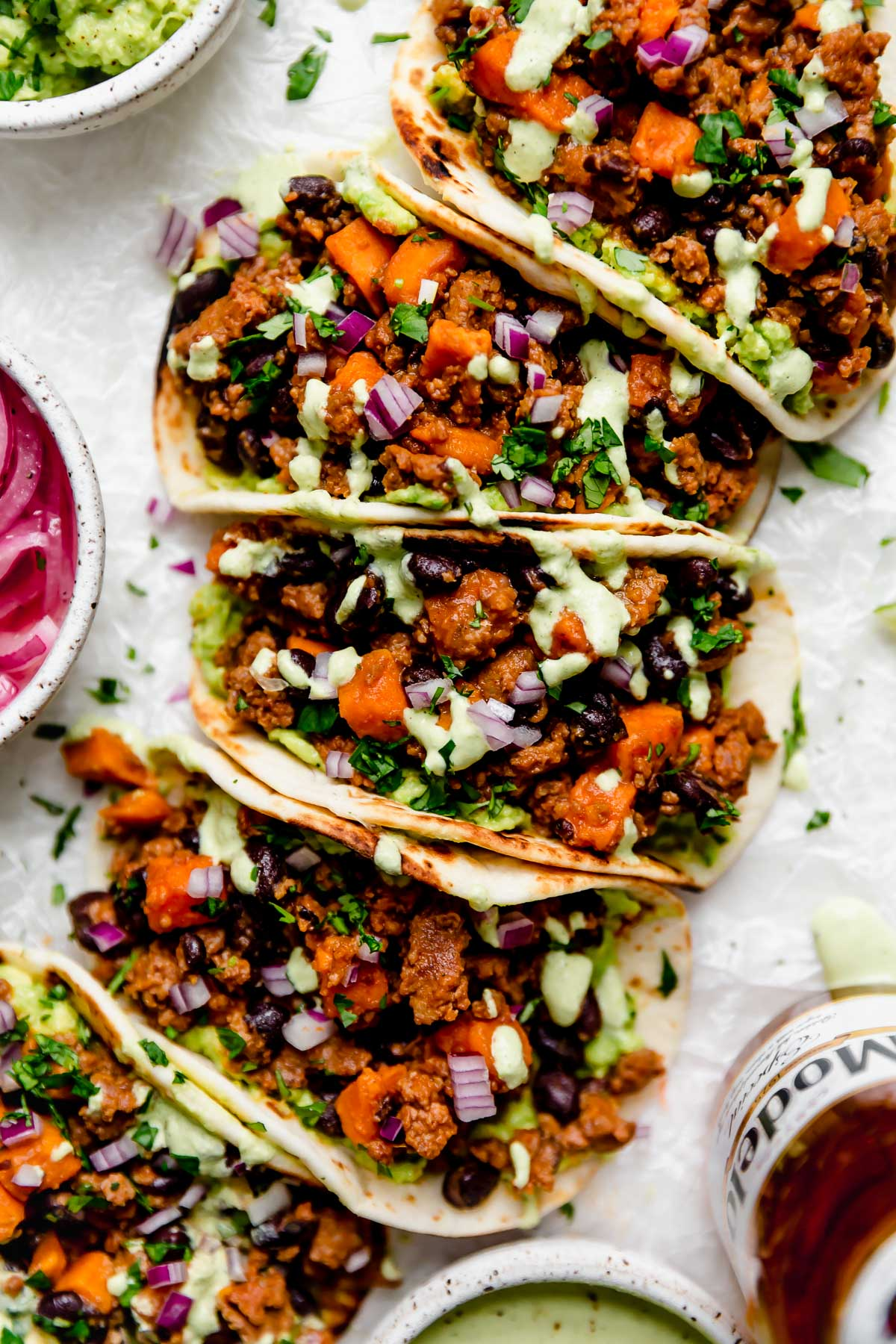 Chorizo Sweet Potato Tacos arranged on a white surface. The tacos are topped with a drizzle of homemade cilantro lime crema. Surrounding the tacos are small bowls of taco toppings (pickled red onions, guacamole, crema, etc.) & a bottle of Modelo beer.