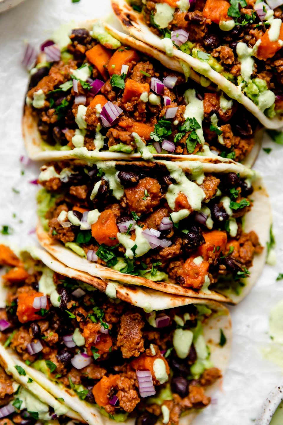 Close up photo of chorizo Sweet Potato Tacos arranged on a white surface. The tacos are topped with a drizzle of homemade cilantro lime crema.