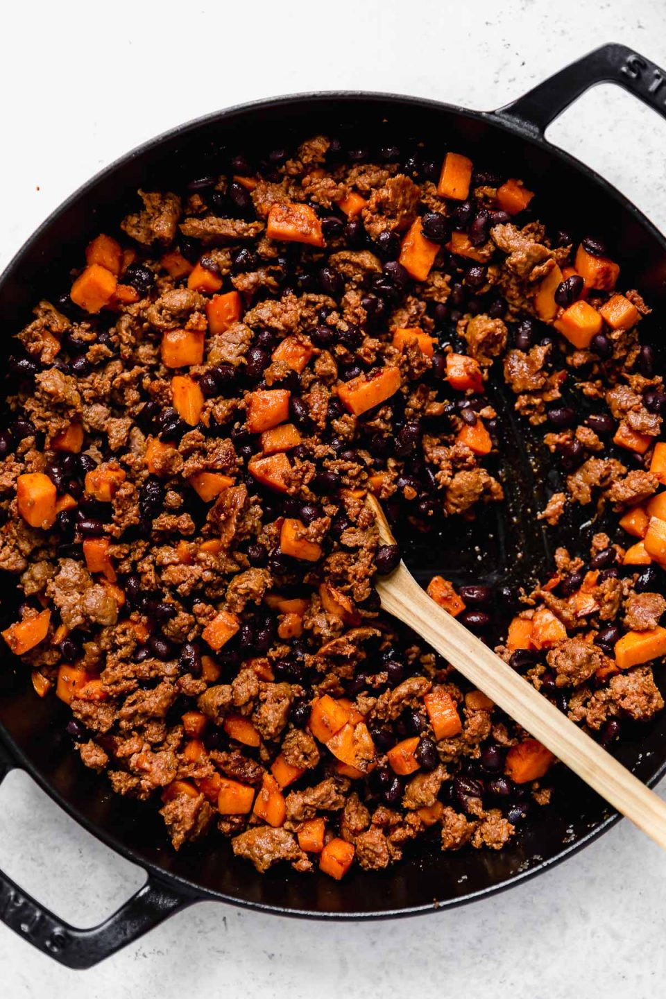 How to make chorizo and potato tacos - Step 2: Adding & mashing black beans into the sweet potato taco mixture.