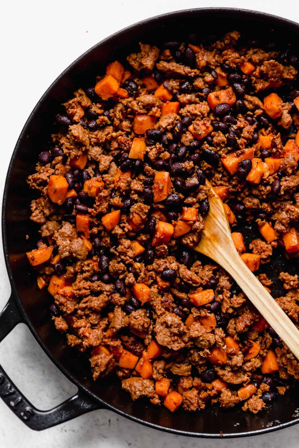 3-Ingredient Chorizo Sweet Potato Tacos filling in a black skillet atop a white surface.