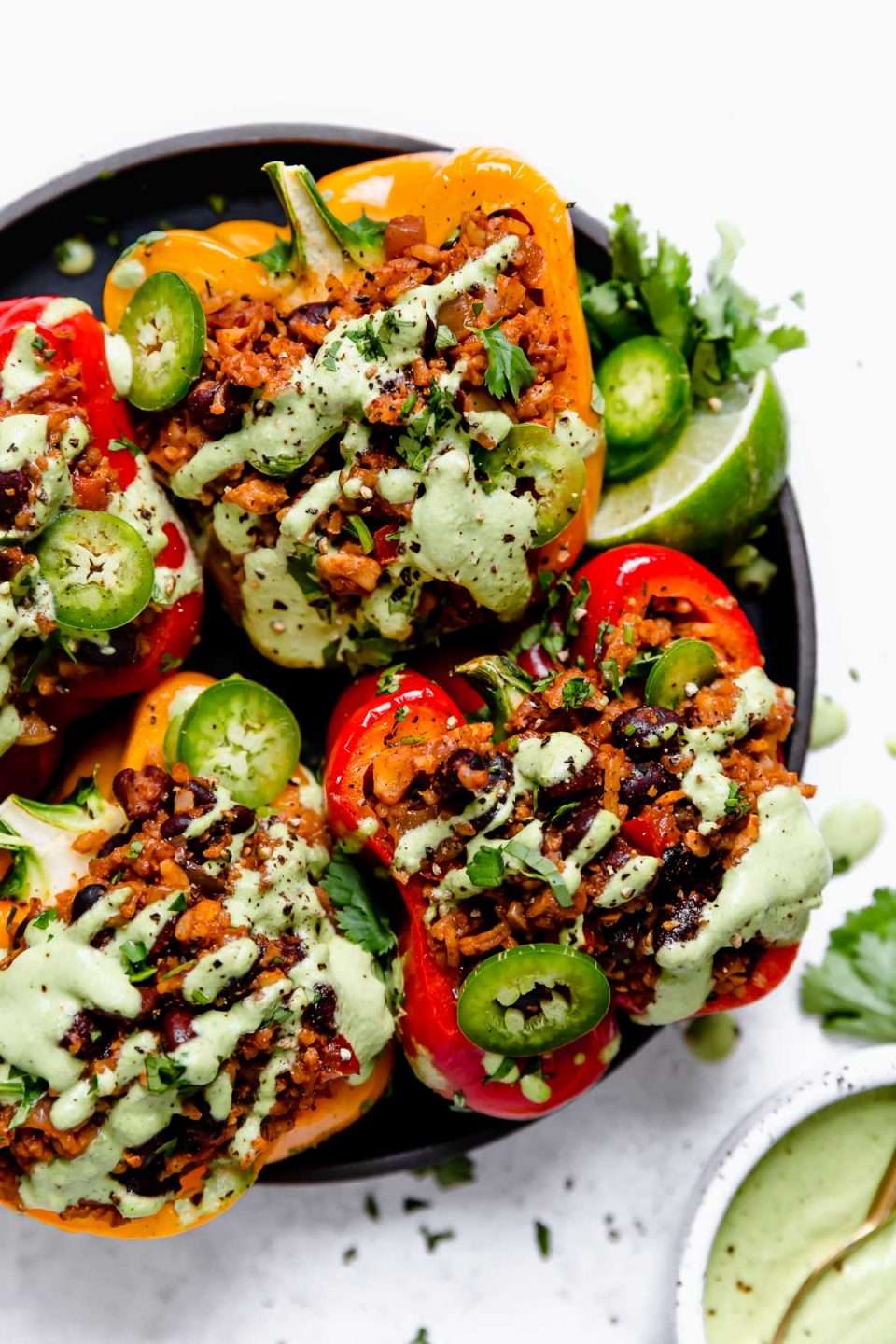 4 Vegan Stuffed Peppers on a small black plate, topped with cilantro lime cashew crema, sliced jalapenos, lime wedges & cilantro.