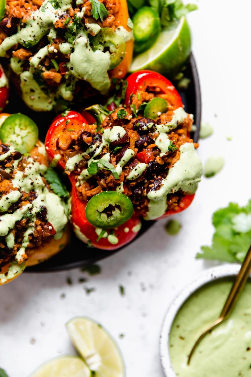 Close up photo of a vegan stuffed peppers on a small black plate, topped with cilantro lime cashew crema, sliced jalapenos, & chopped cilantro.
