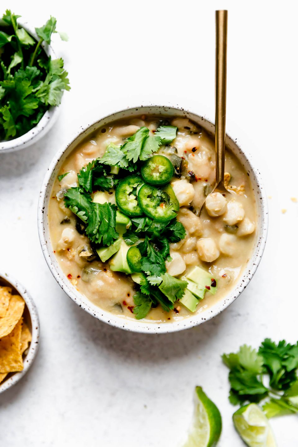 Vegan white chili served in a speckled ceramic bowl, topped with sliced jalapeno, cilantro, & diced avocado. The chili bowl is surrounded by other small bowls with vegan chili toppings, including crushed tortilla strips & lime wedges.