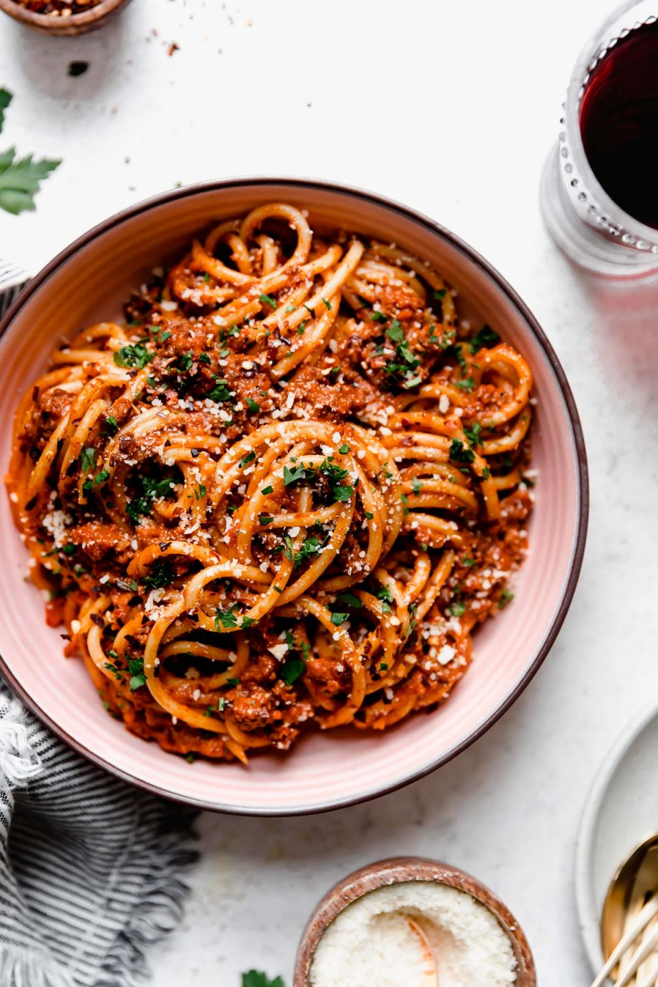 Bolognese sauce tossed into bucatini noodles, served in a pink pasta bowl. The pasta bolognese is topped with grated cheese, chopped parsley, & crushed red pepper flakes, & the bowl is surrounded by red wine glasses, and a striped linen.