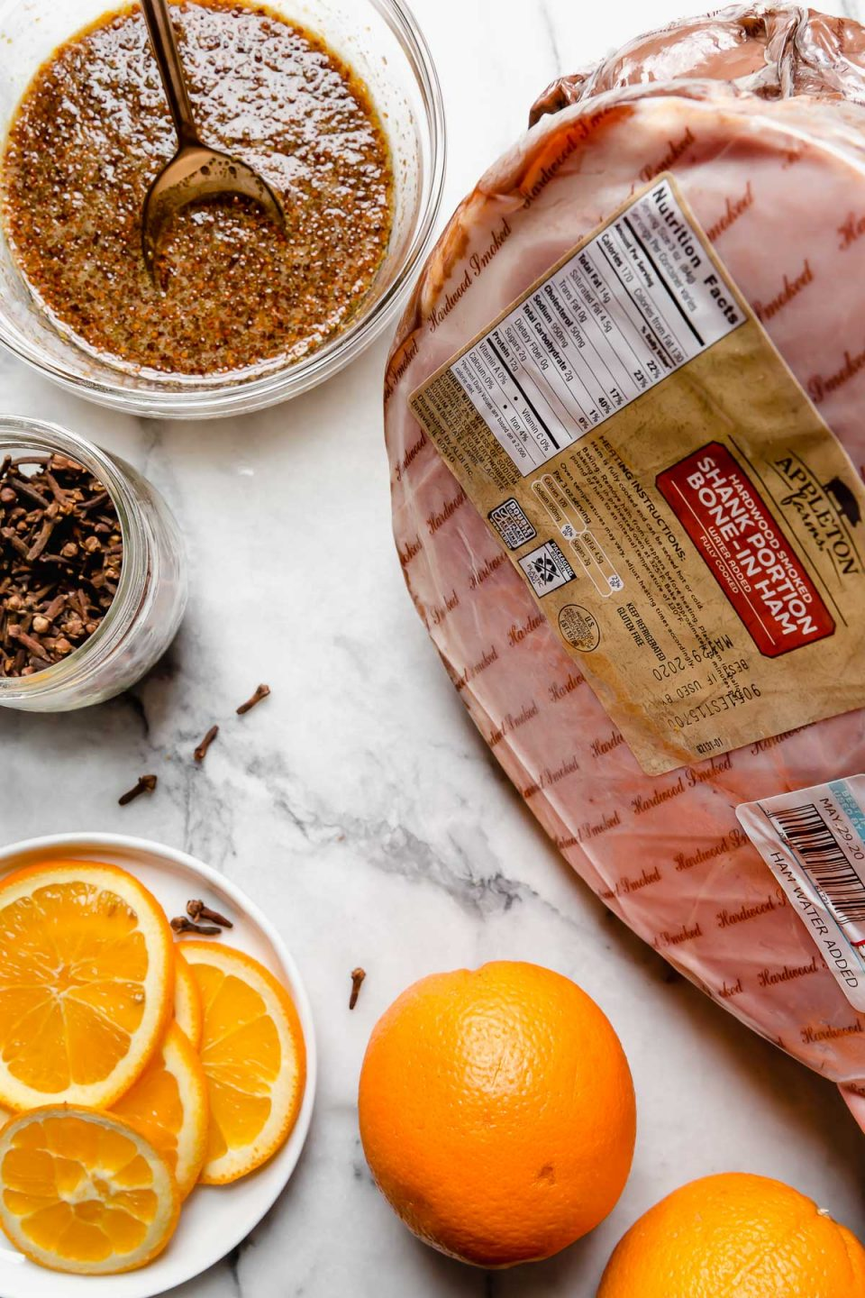 Ingredients for this maple glazed ham recipe on a white marble surface: smoked ham, oranges, cloves & maple glaze.